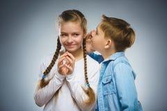 Pojke som viskar i öra av den tonåriga flickan på grå bakgrund svart telefon för kommunikationsbegreppsmottagare Royaltyfri Foto