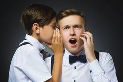 Pojke som viskar i örat av tonåringen eller brodern på grå bakgrund svart telefon för kommunikationsbegreppsmottagare Royaltyfri Fotografi
