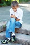 Pojke tio år med mobiltelefonen Royaltyfri Bild