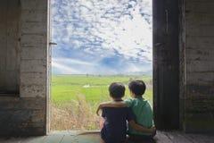 Pojke två sitter i drevet Arkivbild