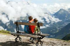 Pojke två sitter på bänk i fjällängar Arkivfoto