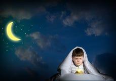 Pojke under räkningarna med en ficklampa Royaltyfria Foton