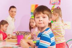 Pojke vid tabellen i dagisgrupp med kompisar Arkivfoton
