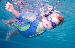 pojkeandedräktholding som simmar undervattens- barn royaltyfri foto