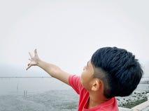 Pojkeanseende av havet som fördelar för att beväpna upp till himmel royaltyfri bild