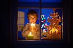 Pojkeanseende för liten unge vid fönstret på tid och att rymma för jul Arkivfoton