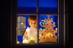 Pojkeanseende för liten unge vid fönstret på tid och att rymma för jul Arkivbilder