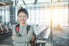 Pojkeanseende i flygplats och leenden Arkivfoton