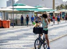 Pojkeanseende med cykeln och med hunden i korg på cykelbanan av den Copacabana stranden royaltyfri foto