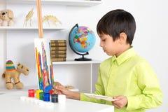 Pojkeattraktionerna på en staffli målar Arkivfoto