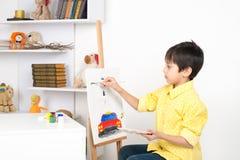 Pojkeattraktionerna på en staffli målar Arkivbilder