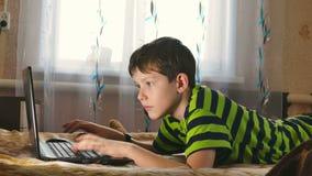 Pojkebärbara datorn som bläddrar internet, spelar att ligga i säng stock video