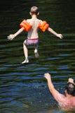 Pojkebanhoppning in i floden Royaltyfri Bild