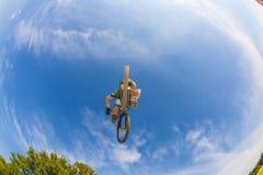 Pojkebanhoppning med hans cykel under den blåa skyen Arkivbilder
