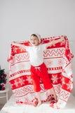 Pojkebanhoppning på sängen som täckas med en filt Arkivbild