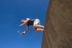 Pojkebanhoppningen slår en kullerbytta blåa Parkour Arkivbilder