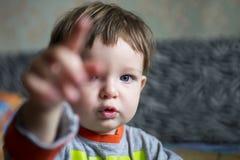 Pojkebarn eller liten unge med den allvarliga framsidan som pekar med hans pekarefinger Pysen pekar riktning vid pekfingret arkivbilder