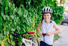 Pojkebarn i den vita cykelhjälmen som blåser upp gummihjulet Royaltyfri Bild