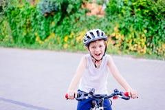 Pojkebarn i den vita cykelhjälmridningen på cykeln Arkivbild