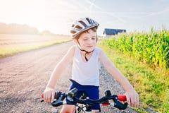 Pojkebarn i den vita cykelhjälmridningen på cykeln Royaltyfri Bild