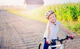 Pojkebarn i den vita cykelhjälmridningen på cykeln Royaltyfri Foto