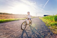 Pojkebarn i den vita cykelhjälmridningen på cykeln Arkivbilder