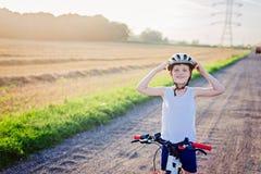Pojkebarn i den vita cykelhjälmridningen på cykeln Royaltyfri Fotografi