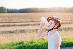 Pojkebarn i vitt cykelhjälmdricksvatten Royaltyfri Foto