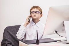 Pojkebarn med en dator, i kontoret i en vit skjortabusine Royaltyfria Foton