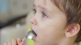 Pojkebarn som äter mat med en sked Framsidan av barnet är närbilden lager videofilmer