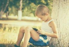 Pojkebarn som spelar med den utomhus- minnestavlaPC:N Arkivfoto