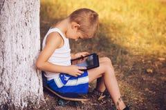 Pojkebarn som spelar med den utomhus- minnestavlaPC:N Arkivfoton