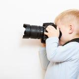Pojkebarn som spelar med kameran som tar fotoet Arkivbild