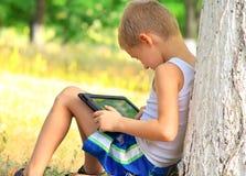 Pojkebarn som spelar med minnestavlaPC Royaltyfri Foto