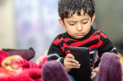 pojkebarn som spelar med mobiltelefonen Royaltyfri Bild