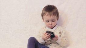 Pojkebarn som spelar med telefonen på sängen lager videofilmer