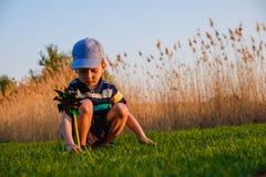 Pojkebarn som spelar med väderkvarnen i grönt gräs av stranden på begreppet för sommarsemester för frihet Arkivbilder
