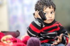 pojkebarn som talar över mobiltelefonen Arkivbilder