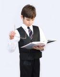 pojkebarneleven läser skolaläroboken Arkivfoto