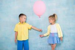 Pojkebarnet ger en ballong till en flicka Tecken av uppmärksamhet, sympati och kurtis arkivfoto