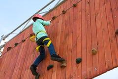 Pojkebarnmoment på avsatserna på den vertikala väggen på hinderkursen i nöjesfältet, utomhus- aktiviteter, vaggar klättring Arkivbild