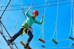 Pojkebarnmoment på träbräden på hinderkursen i ett nöjesfält, utomhus- aktiviteter, vaggar klättringen, fara, utbildning, royaltyfri fotografi