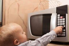 Pojkebarnunge som spelar med tidmätaren av mikrovågugnen fotografering för bildbyråer