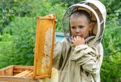 Pojkebeekeeperen sparar ny honung från en honungcell på en bikupa Ny honungbiodling Arkivbilder
