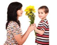 pojkeblommor ger hans små mom till Arkivfoto