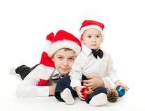 Pojkebröder, i santas att krama för hattar Royaltyfri Fotografi