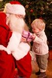 pojkeclaus gåva som ger santa till Arkivfoton