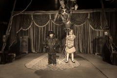 Pojkeclown på etapp med flickainnehavballonger royaltyfri foto
