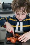 pojkecuttingtomat Fotografering för Bildbyråer