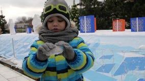 Pojkedet fria rymmer is i hans händer mot bakgrunden av julträd arkivfilmer